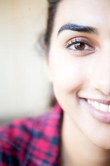 Половина лица женщины с красивой улыбкой