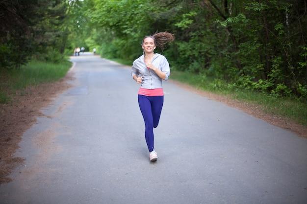Счастливый молодая женщина, бег трусцой и улыбается в парке