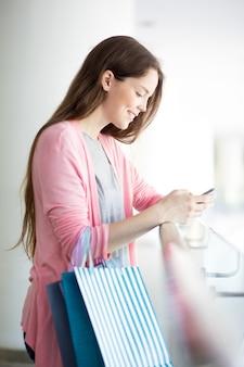 モールでスマートフォンを使用して笑顔の若い女性