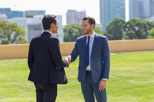 Два улыбающихся деловых людей, пожимая руки на открытом воздухе