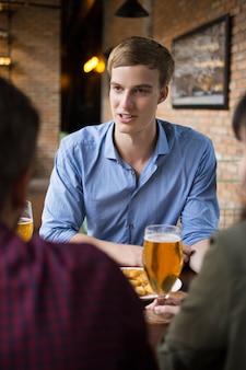 Молодой человек пили пиво с друзьями в паб