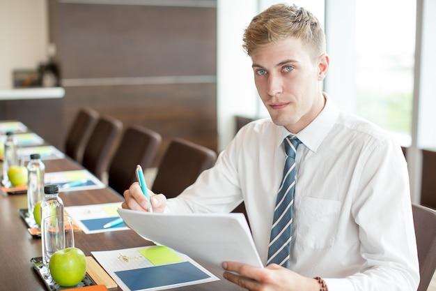 会議のテーブルでスピーチを準備するビジネスマン