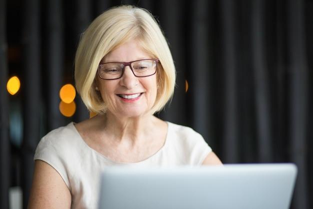 ラップトップで働く笑顔のシニア女性の拡大写真
