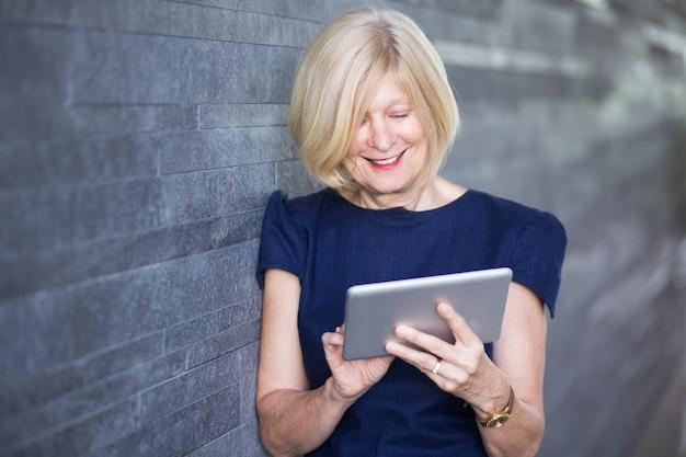 デジタルタブレットを使用している幸せな高齢の実業家