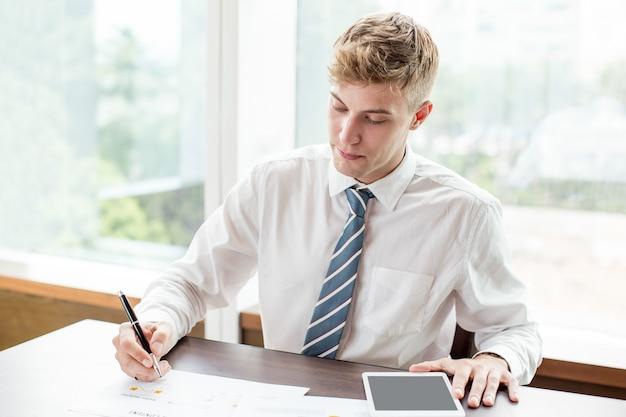 深刻な若いビジネスマンは、オフィスデスクで働いて