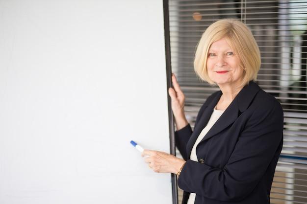 Улыбающийся старший бизнес-леди проводит семинар