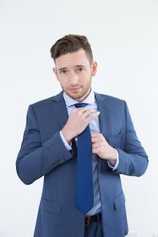 傲慢なハンサムな若いビジネスマン調整のネクタイ