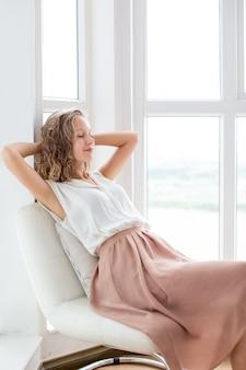 Красивая женщина, дремлющая на стуле на лоджии