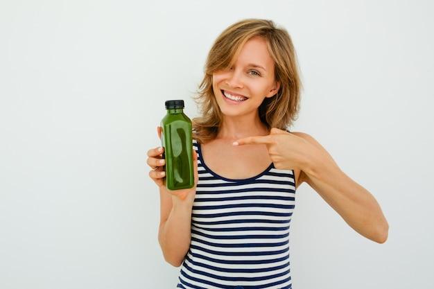 緑色のボトルを指す朗らかな若い女性