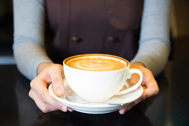Крупным планом женские руки, проведение чашки кофе