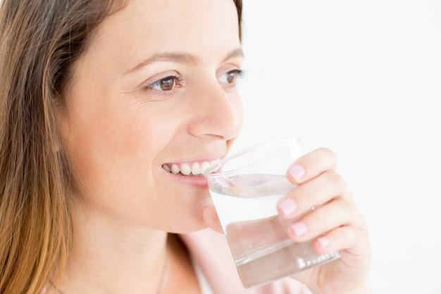陽気な若い女性の飲料水のクローズアップ