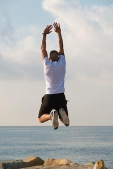 空中に腕を上げた筋肉の男性
