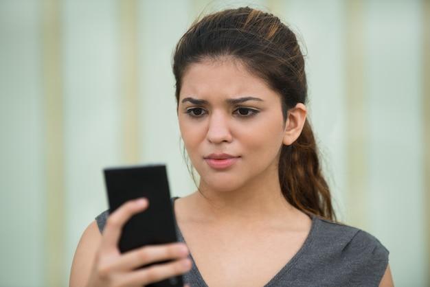 若い女性が携帯電話でメッセージを読み上げる