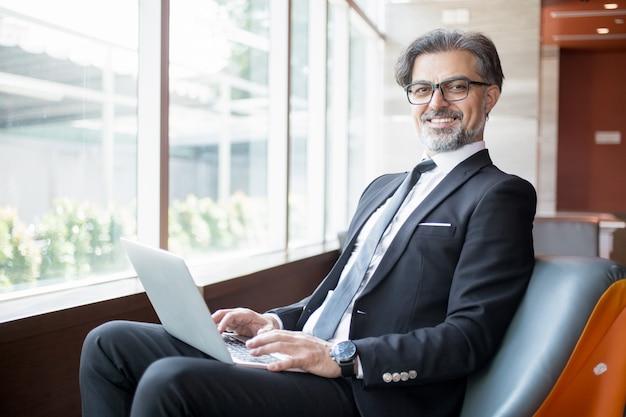 幸せなビジネスリーダー、ロビーでタブレットを使用する