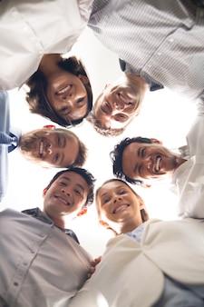 一緒に頭を持つ幸せなビジネスの人々