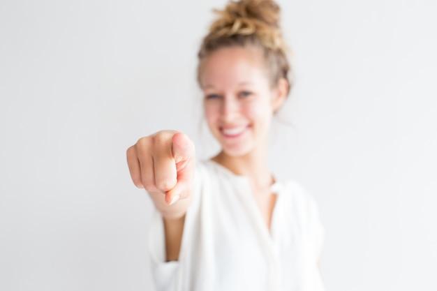 あなたを指差している幸せな若い素敵な女性