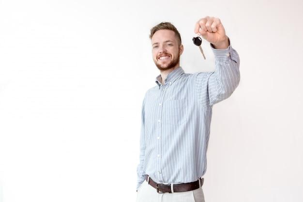 Счастливый менеджер по продажам, держащий автомобиль или ключ дома