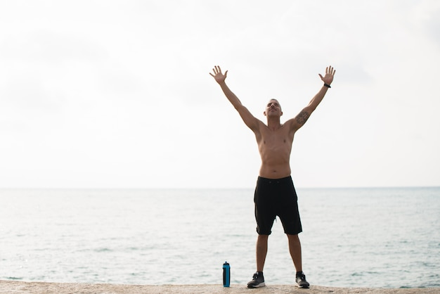 Счастливый спортсмен, наслаждаясь обучением на берегу
