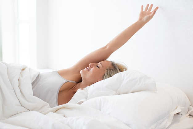 眠った後にベッドでストレッチする幸せな若い女性