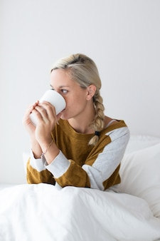 病気の女がベッドに座って飲み物を飲む