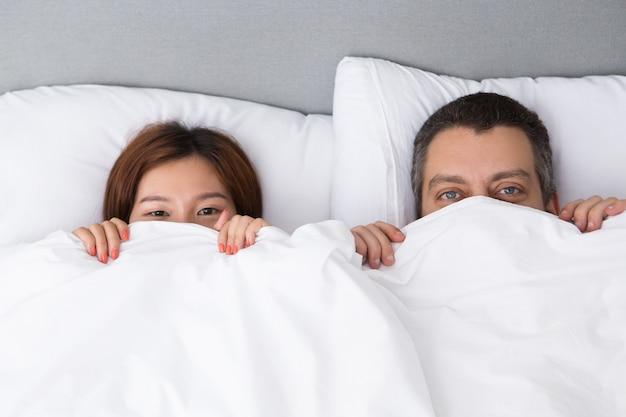 羽毛布団の後ろに隠れている若いカップル