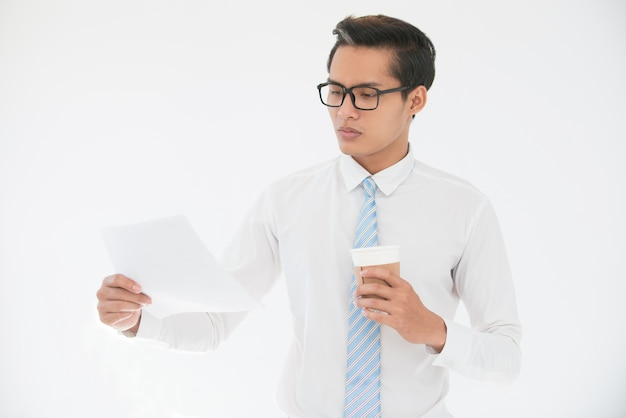 Серьезный азиатский деловой человек, читающий документ