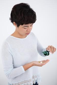 Серьезная азиатская женщина, наливая таблетки из бутылки