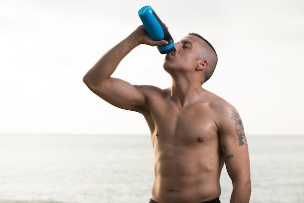 シャツレスの若い男の飲料水