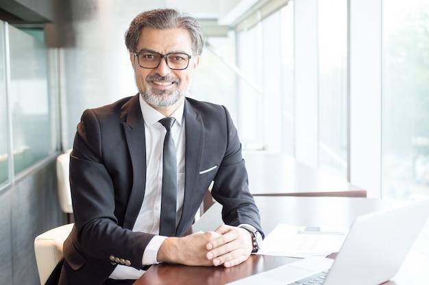 オフィスデスクで座っている笑顔のビジネスリーダー