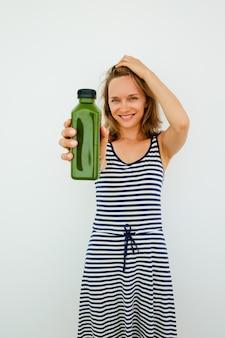 Улыбается красивая молодая женщина, используя естественный шампунь и показ продукта для камеры. счастливая девушка питьевой коктейль, чтобы быть здоровым. концепция выбора