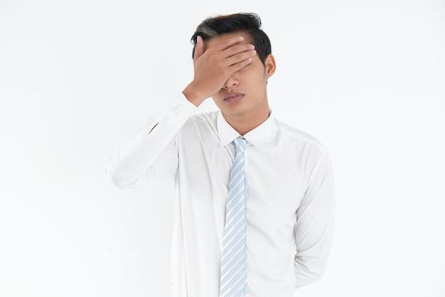 Подчеркнутый молодой азиатский бизнесмен, охватывающий глаза