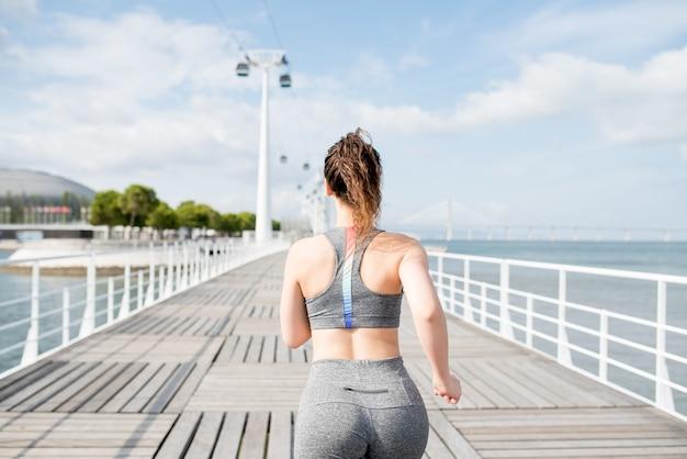 Привлекательная спортивная женщина, бегущая по мосту