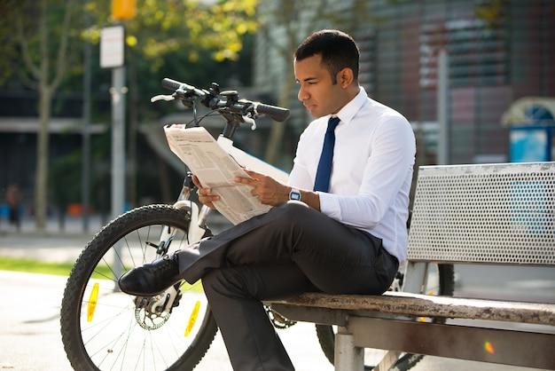 Концентрированный менеджер, читающий газету на открытом воздухе
