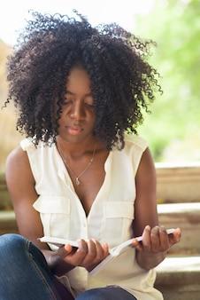 Концентрированная женщина, читающая книгу на открытом воздухе