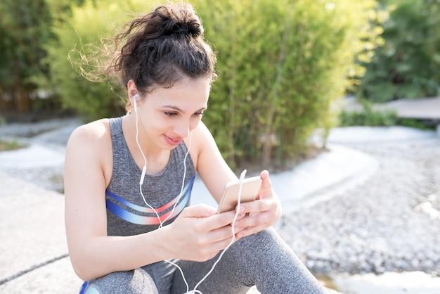 Контент спортивная девушка, слушающая музыку в парке