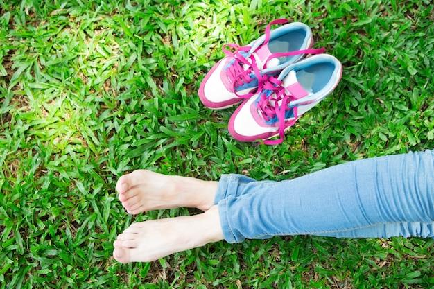 Обрезанный вид девочек ноги и кроссовки на траве