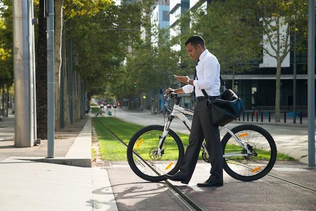 Испаноязычный офисный работник с велосипедом и телефоном на улице