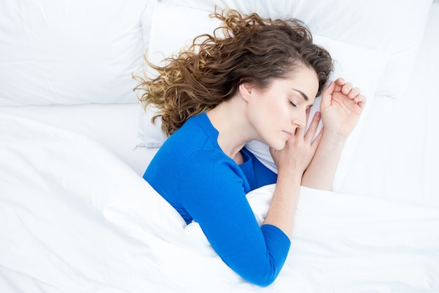 ベッドで寝る中年の美しい女性