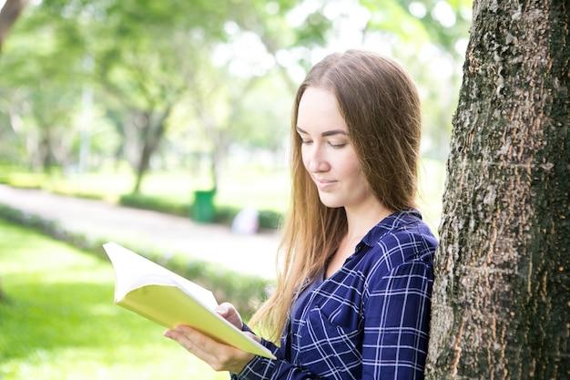 公園で読書を楽しむ平和な女性のブックワーム