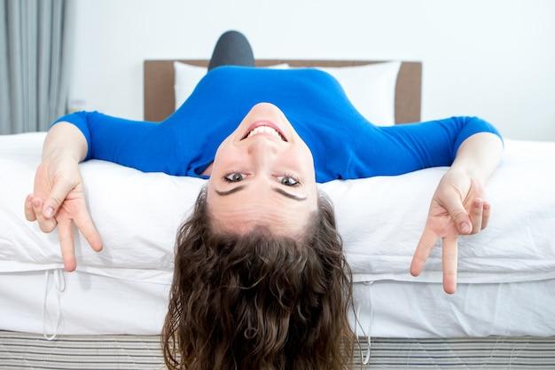 Игривая женщина, показывающая знаки победы на кровати