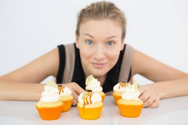 カップケーキを味わうために提供する陽気な女性