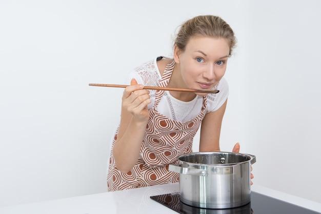 キッチンでホットスープをテストしているかなり若い女性