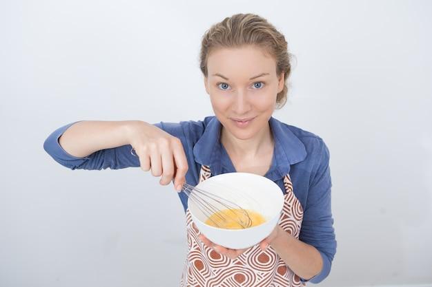 満足のいく若い主婦が調理方法を示している