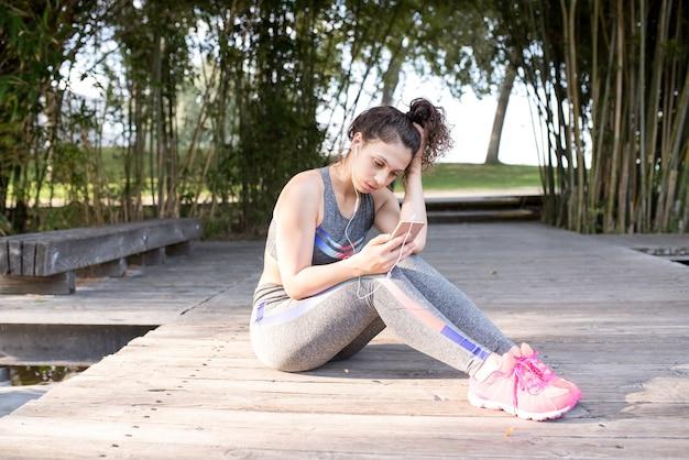 深刻なスポーティな女の子は公園で音楽を聴く