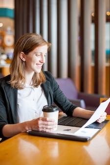 カフェで仕事をしてコーヒーを飲む笑顔の女性