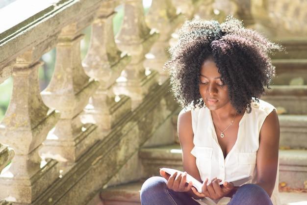 公園の階段で若い黒人女性読書