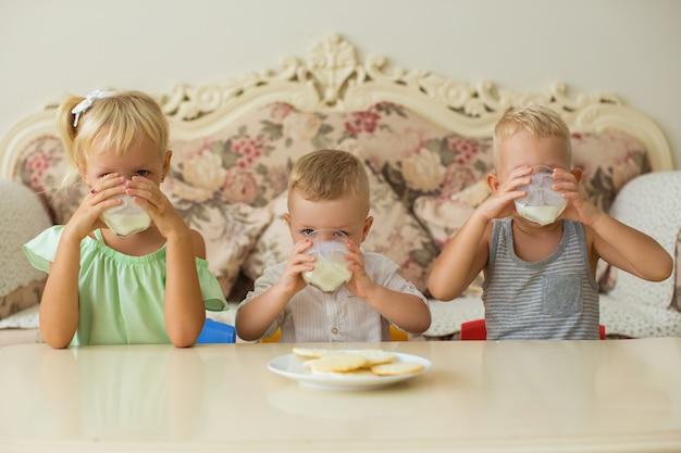 小さな男の子と女の子が家で牛乳を飲む