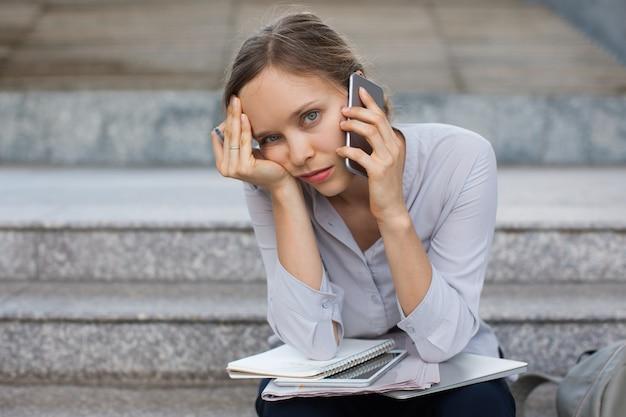 ペーパーと電話で座っている疲れたビジネスマン