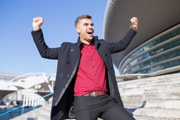 Возбужденный молодой бизнесмен торжествует на открытом воздухе