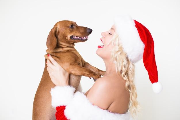 愛する犬を持つサンタの帽子の幸せな女性